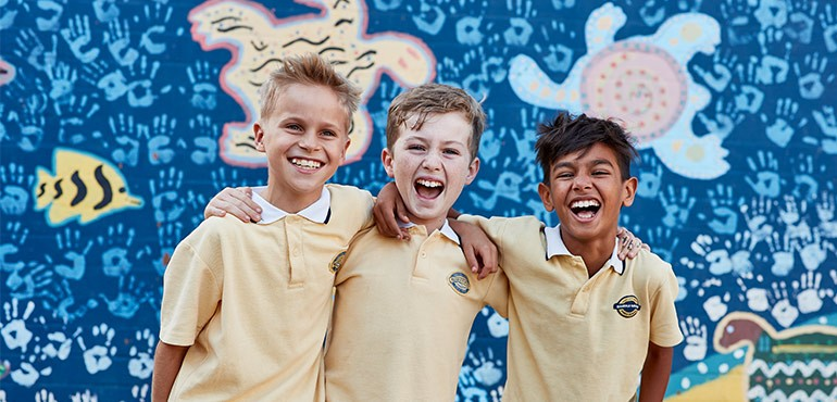 Three boys smile with their arms around each other.
